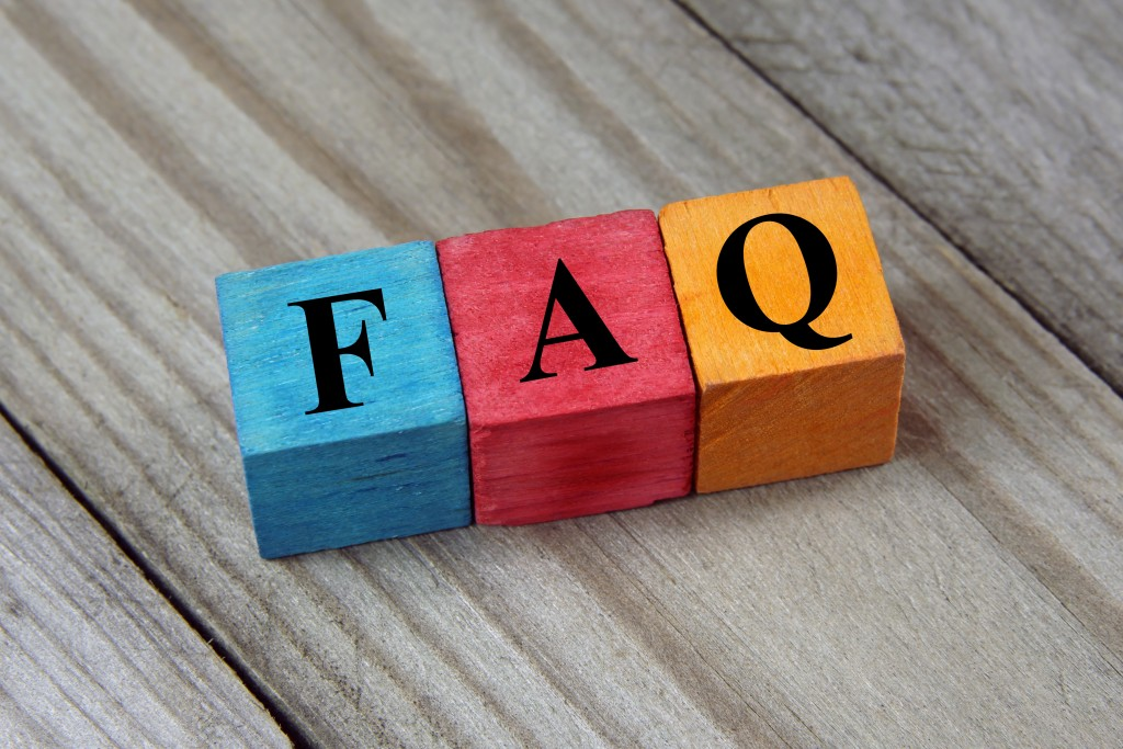 Colourful blocks with letters on them lying on a wooden table spelling out FAQ, meaning frequently asked questions