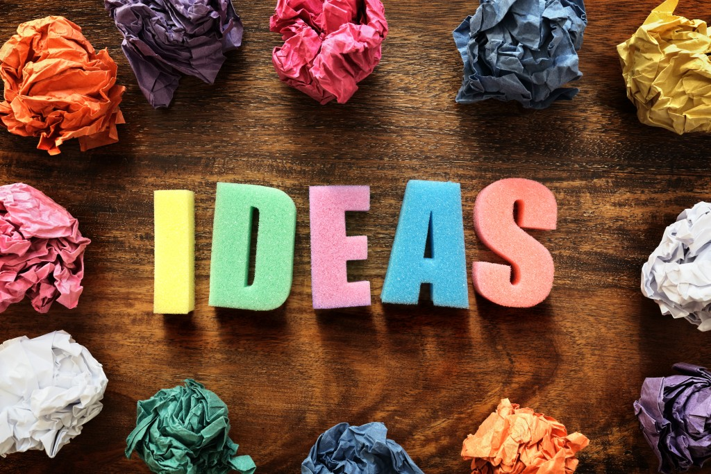 """Colourful magnet letters lying on a wooden table spelling out the word """"ideas"""", surrounded by screwed up balls of colourful paper."""