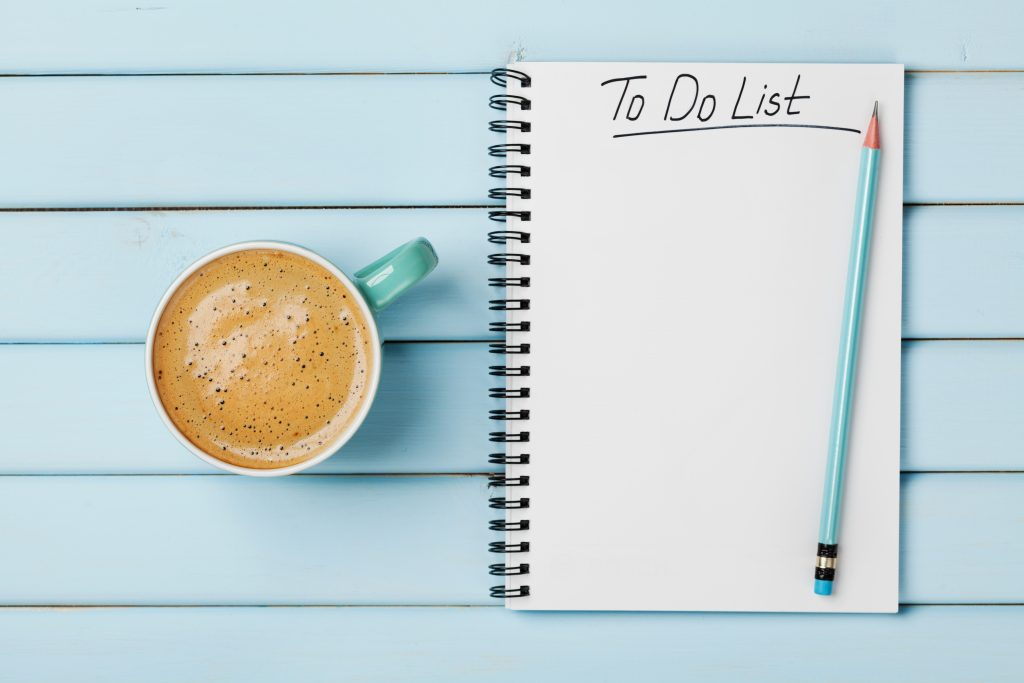 To do list words written at the top of a notepad with blank space ready for the list underneath. Pad is on a blue table with a coffee and pencil next to it.